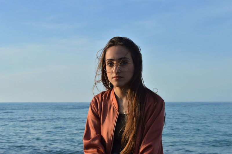 Young Woman By Sea Against Sky