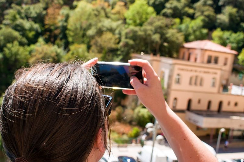 Rear view of woman photographing from smart phone