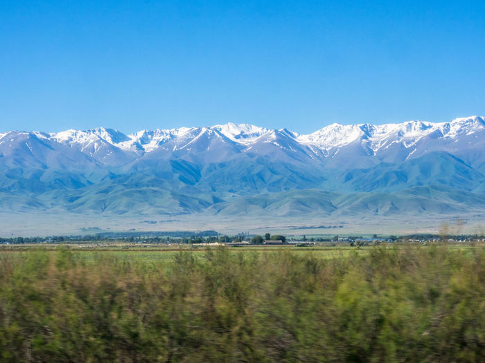 View of the mountains of Kyrgyzstan, as seen from the Almaty-Aktau railway in the Kazakhstan steppe Beauty In Nature Landscape Mountain Mountain Range No People Scenics - Nature Snowcapped Mountain Steppe