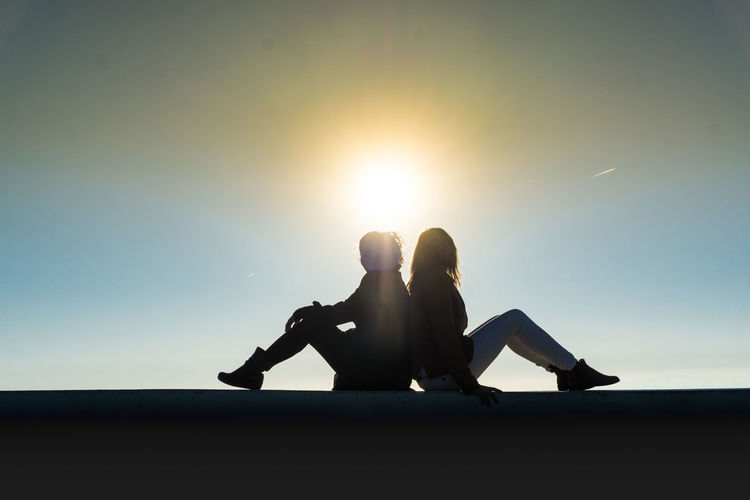 Silhouette women sitting on rock against sky during sunset