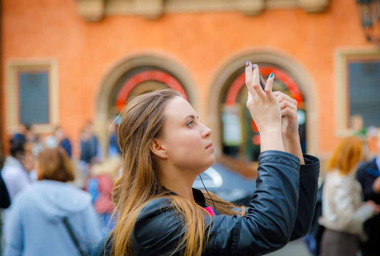 A young girl travels and takes pictures of the sights of the city on the phone