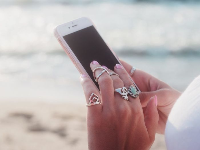 Close-Up Of Woman Using Mobile Phone At Beach
