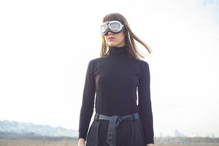 Young woman with sand goggles standing alone in the desert Alone Desert Goggles Trip Adventurer Attractive Aviator Beautiful Woman Casual Clothing Day Front View Lifestyles Model Outdoors Particles person Pilot Posing Sand Sky Standing Style Vintage Windy Young Adult