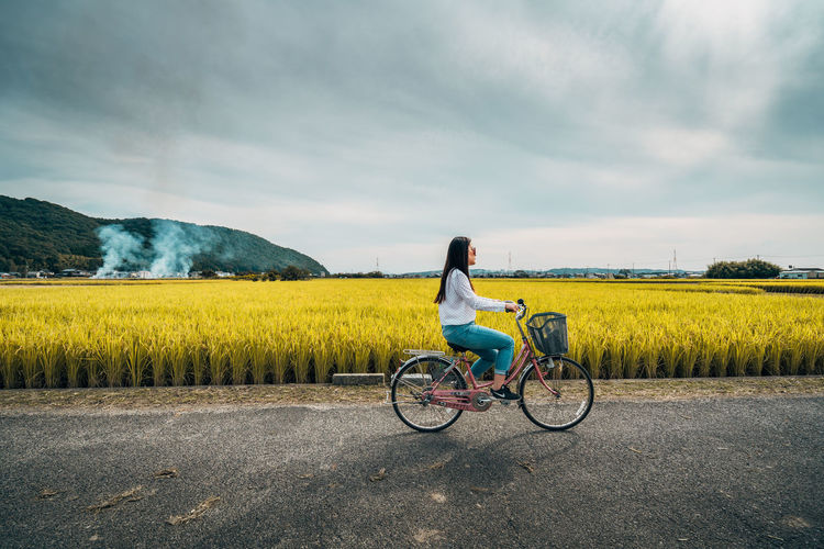 Side View Of Woman Cycling On Footpath By Field