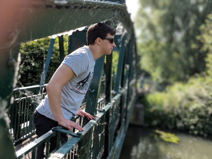 Side view of young man on footbridge over canal