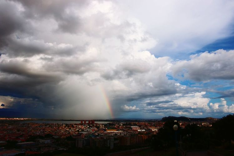 Aerial view of rainbow over buildings in city