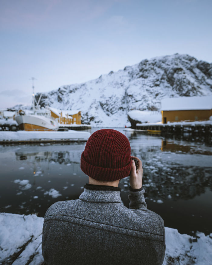 Rear view of man photographing lake while standing against sky during winter