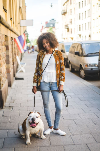 Full length of woman with dog on street in city