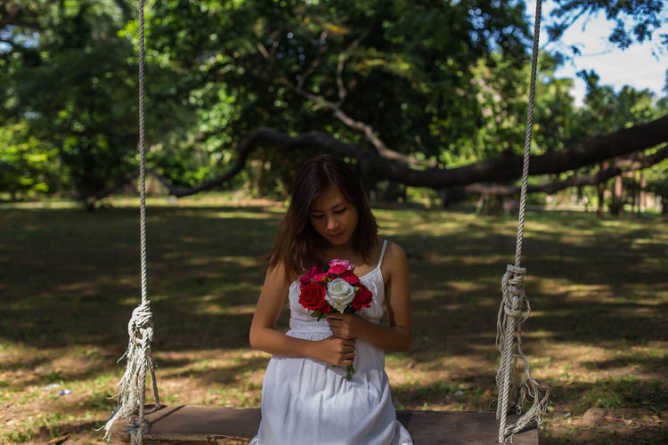 Young woman holding roses sitting on swing at land