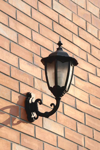 Black Lantern mounted on brown brick wall in exterior. Lighting Equipment Built Structure Architecture Building Exterior No People Wall Brick Brick Wall Wall - Building Feature Street Light Pattern Street Low Angle View Electric Lamp Black Color Day Mounted Outdoors Light Black Lantern Lantern Lanterns Lantern Light Brown Bricks Brown Brick