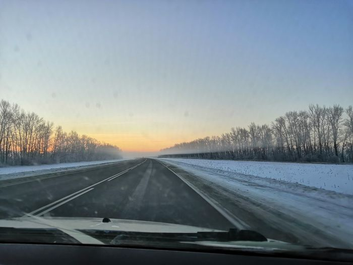 Road seen through car windshield during winter
