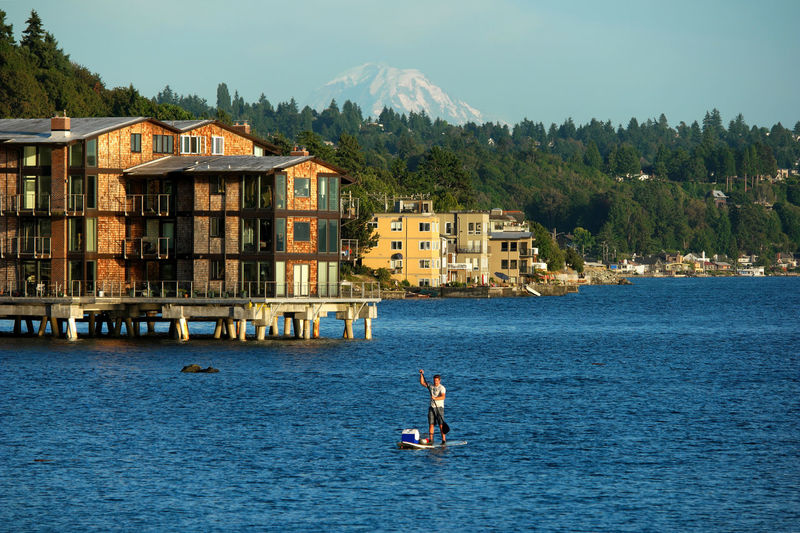 Man paddleboarding on lake with buildings in background