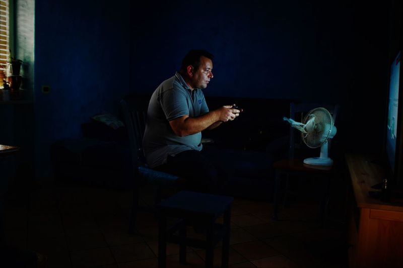 Man holding remote control against electric fan in darkroom