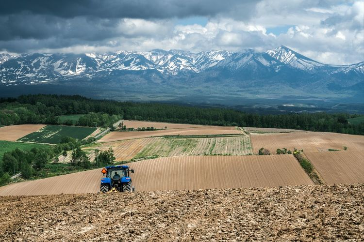 Tractor ploughing farmland on rolling hills against a mountain backdrop