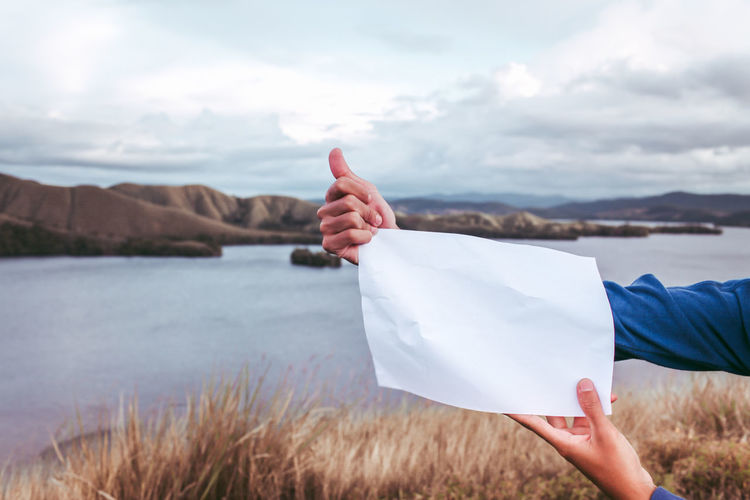 Cropped Hands Of Man Holding Paper At Lake Against Sky