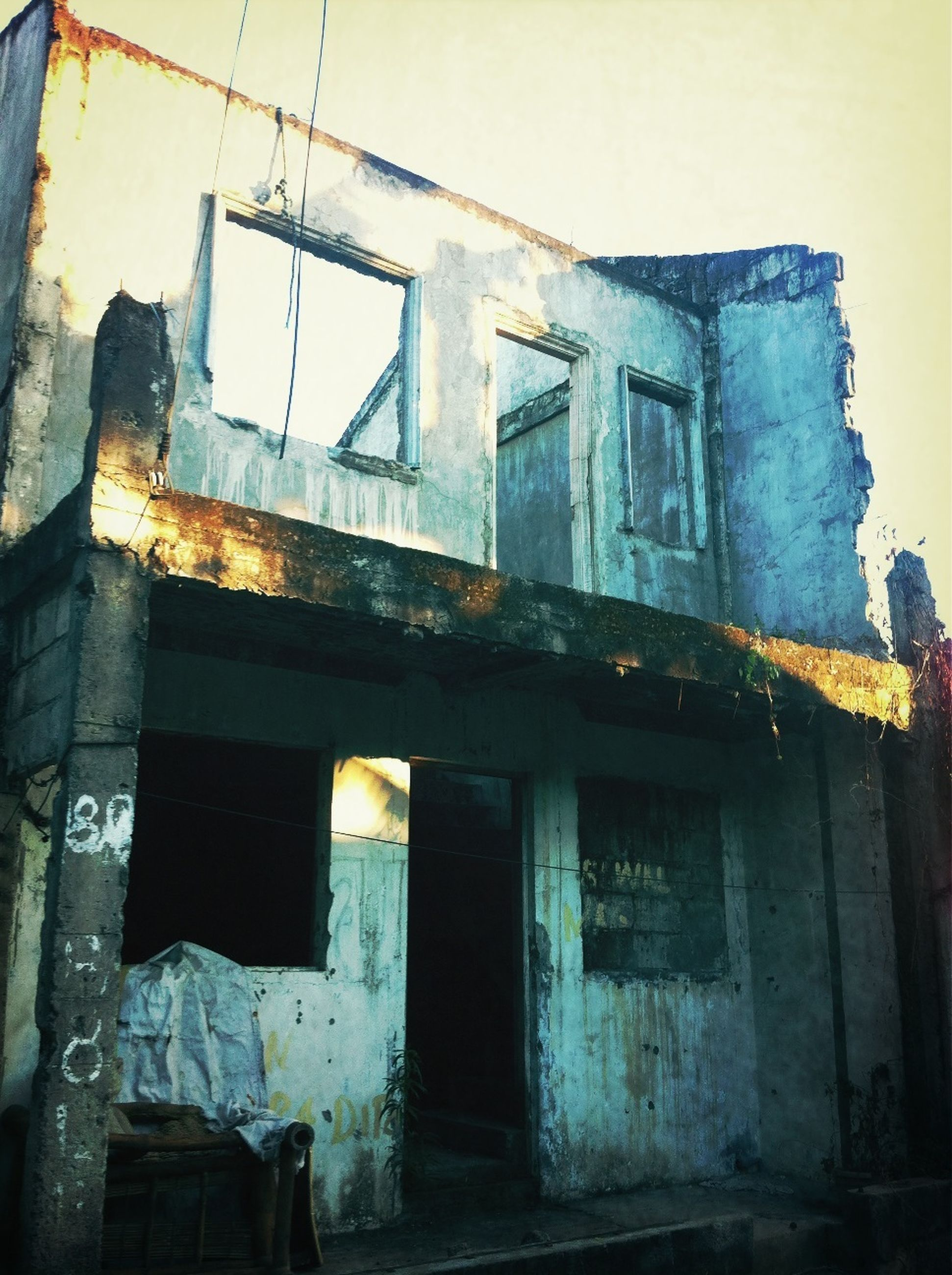 architecture, building exterior, built structure, window, abandoned, house, old, low angle view, damaged, obsolete, residential structure, residential building, weathered, run-down, deterioration, building, bad condition, door, sky, no people