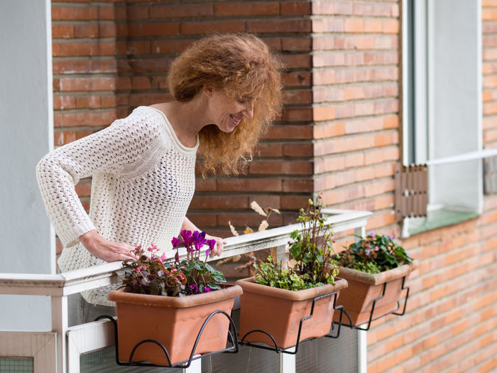 Woman standing by potted plant on table