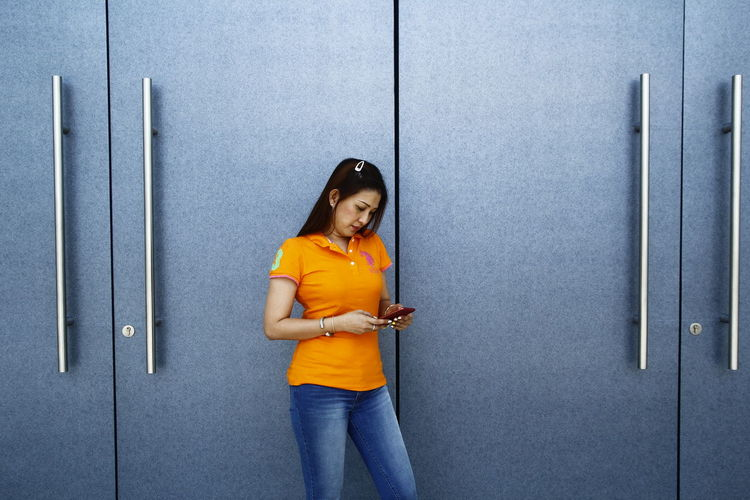 a lady uses her phone in front of a blue colored door Blue Call Cellphone Communication Door Girl Lady Orange Smartphone SMS Technology Telecommunication Text Wall Woman