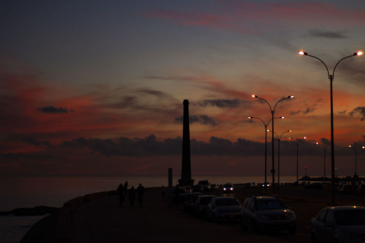 Cars On Street By Sea Against Sky During Sunset