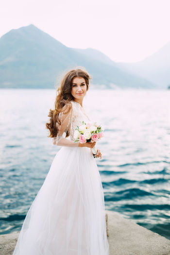Full length portrait of woman with bouquet standing against lake