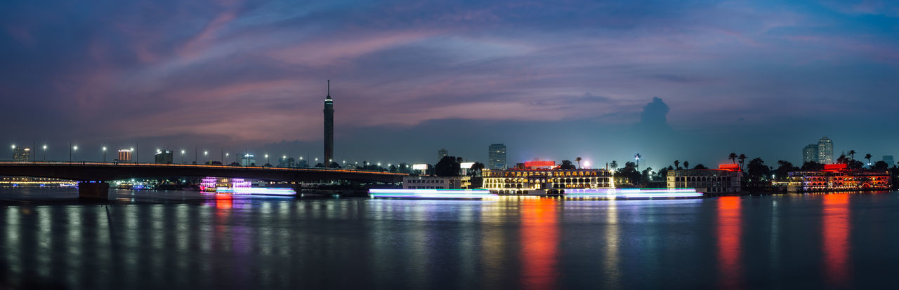 Panoramic of Cairo city center at night, long exposure with light trails of moving boats on the Nile river. Water Architecture Sky Reflection Cloud - Sky Illuminated City River Waterfront Dusk Night Building Travel Destinations Tower Transportation Outdoors Cityscape Skyscraper Cairo Egypt Zamalek Boat Nile River