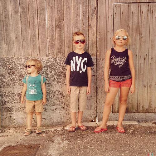 Portrait of siblings standing against wooden fence