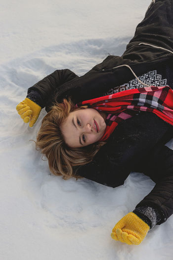 Portrait of smiling girl lying in snow