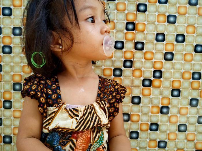 Cute girl sucking pacifier against wall