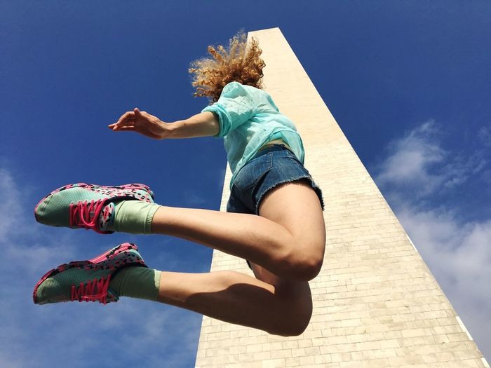 Low angle view of young woman jumping by building against sky