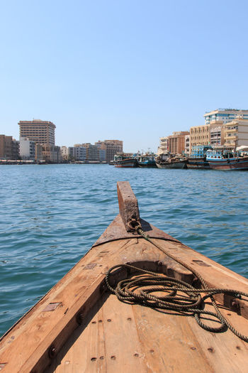 Dubai, UAE - October 08, 2014: People are commuting and using traditional wooden boat at dubai creek of UAE Architecture Boat Building Exterior Built Structure City Clear Sky Day Dubai Dubai Creek Emirates In Front Of Moored Nautical Vessel Obsolete Old Rich River Riverbank Rowboat Sea Tourists Travel Destinations United Arab Emirates Water Weathered