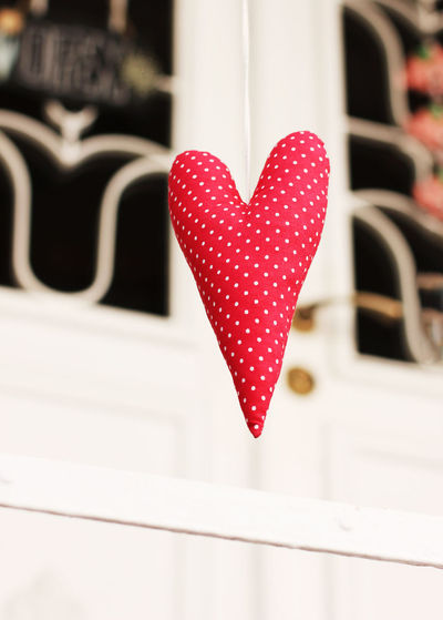 Low angle view of red polka dotted heart shape decoration hanging outdoors