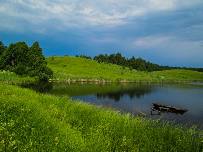 Scenic view of lake by grassy hill against cloudy sky