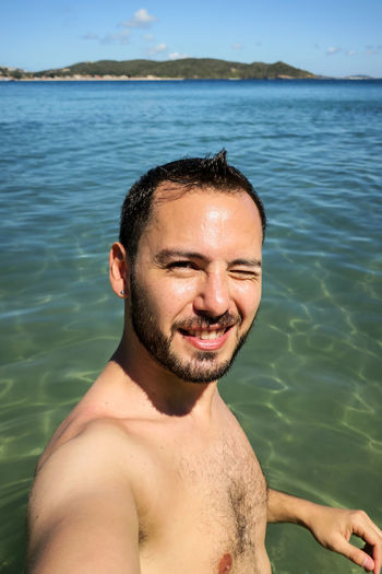 Portrait of young man smiling in sea