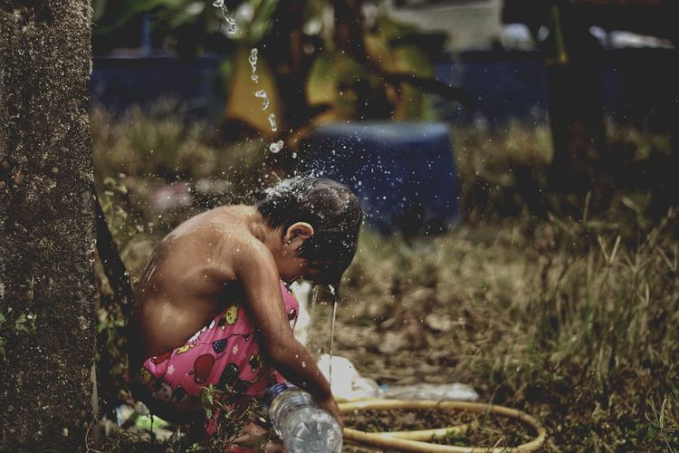 Shirtless girl crouching under falling water in village