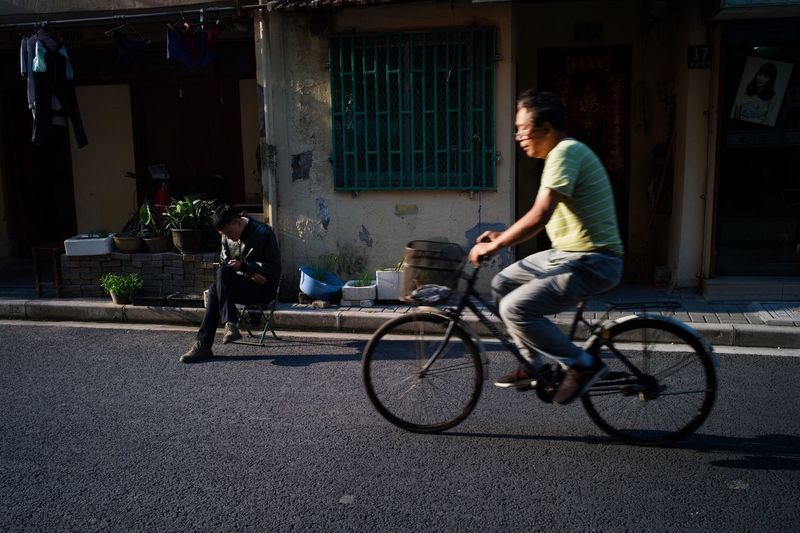 Side view of man riding bicycle on street