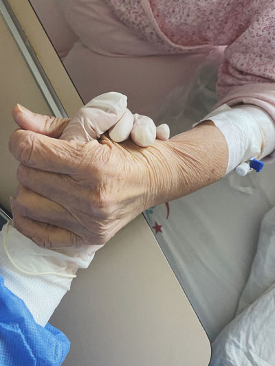 Midsection of senior patient holding hand of doctor