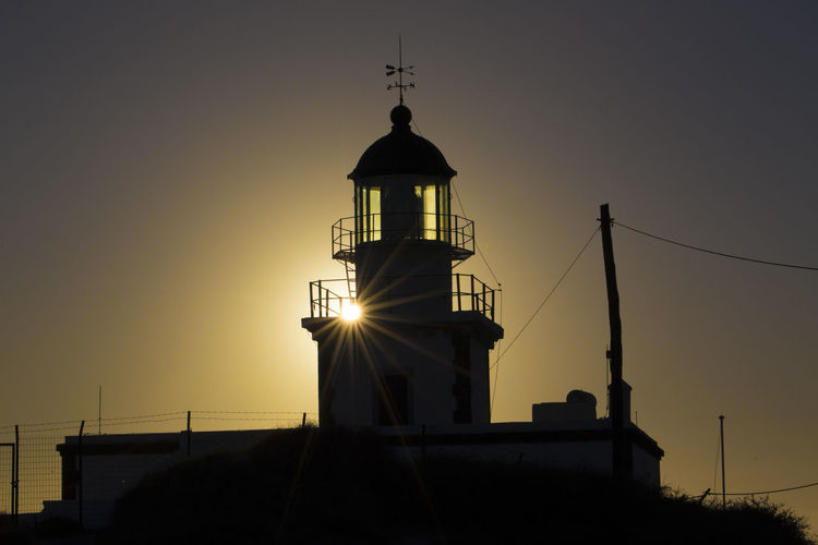 Low angle view of silhouette lighthouse by building against sky during sunset