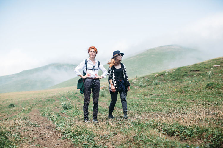 Adventure Adventure Club Backpack Beauty In Nature Casual Clothing Day Female Field Friends Friendship Girl Grass Hike Hiker Landscape Lifestyles Mountain Nature Non-urban Scene Path Road Sister Sisters Sky Tranquil Scene