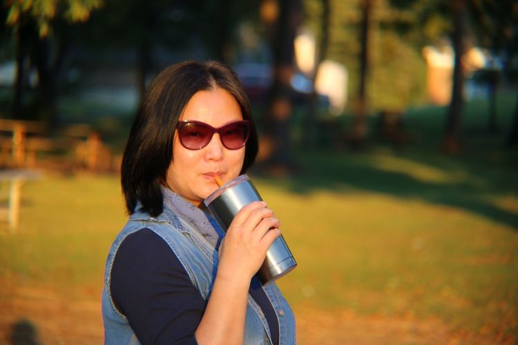 Portrait of woman wearing sunglasses while having drink in park