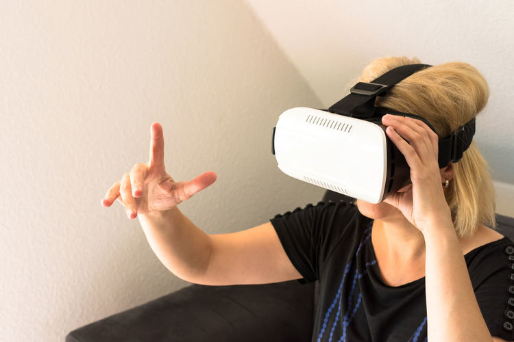 Woman pointing white using virtual reality simulator at home