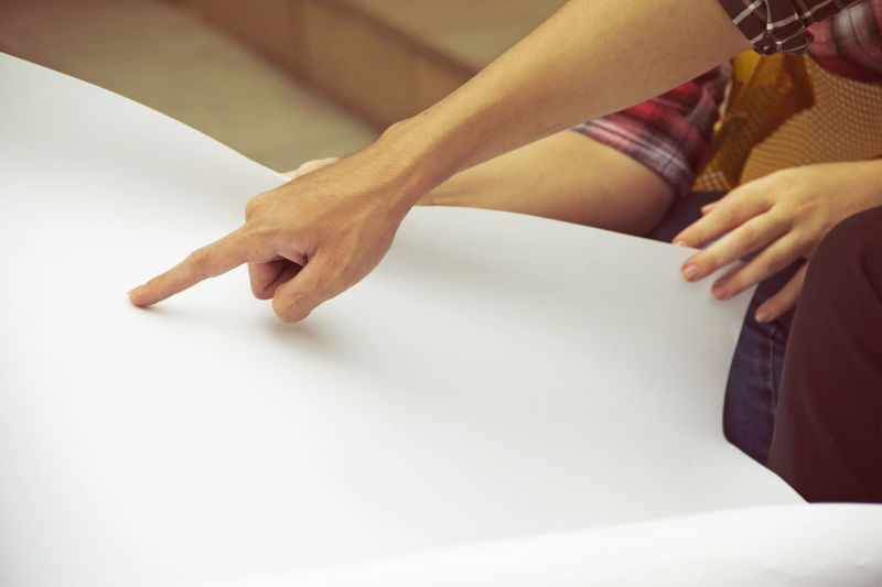 Cropped hand of woman pointing on blank paper at home