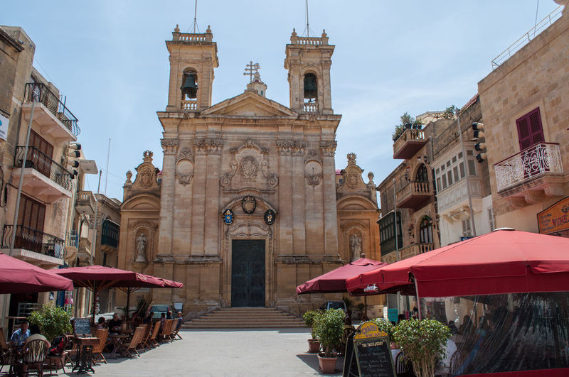 St. George's Basilica church, Gozo in Malta. Built in 1678 Gozo Island Malta Shade St. George's Basilica Worship Architecture Belief Building Exterior Built 1678 Cafe City Dining Incidental People Outdoors Place Of Worship Prayer Religion Restaurant Saint Georges Spirituality Street Travel Travel Destinations Umbrella Victoria Gozo