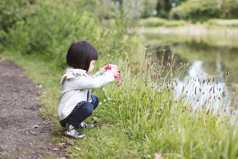 Side view of a girl taking photo  on field