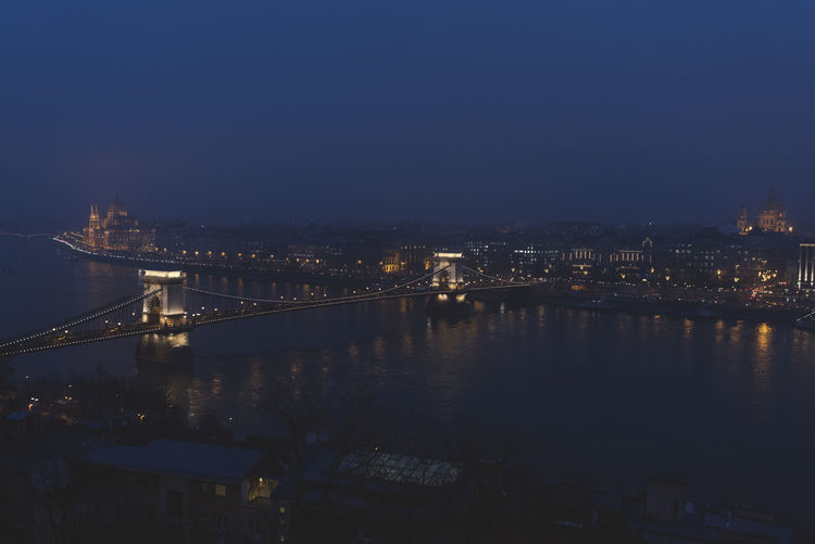 Nighttime skyline of the historic city of Budapest on a foggy Cathedral and Chain Bridge crossing the Danube River Architecture Bridge Bridge - Man Made Structure Building Exterior Built Structure Chain Bridge City Cityscape Connection Dusk Illuminated Nature Night No People River Sky Suspension Bridge Transportation Travel Destinations Water