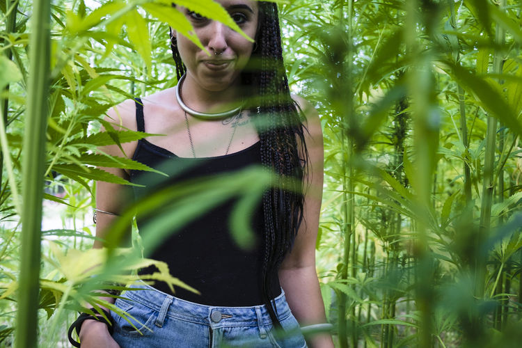 Portrait Of Smiling Young Woman Standing Amidst Cannabis Plants