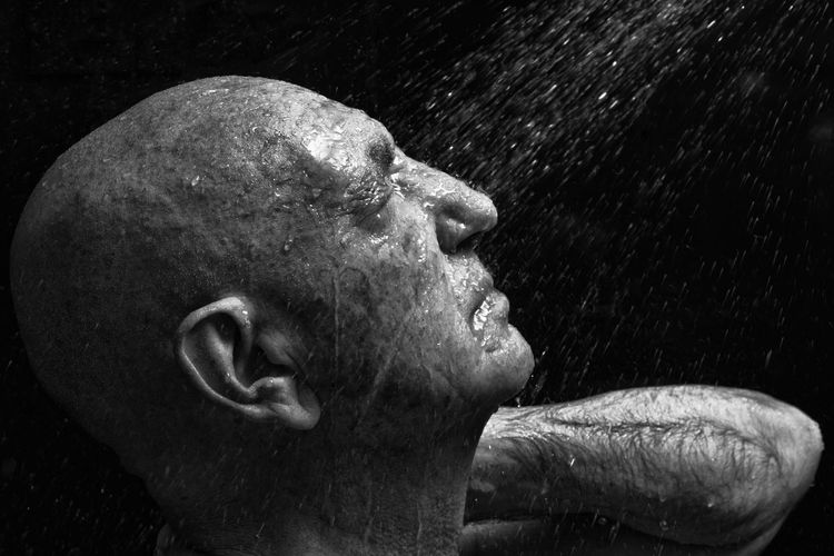 Side view of man taking shower