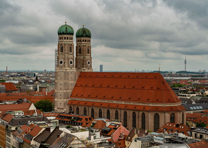 Munich, Bavaria, Germany - May 29, 2019. General aerial view of Munich from a tower, featuring the two towers of the Frauenkirche on a partly cloudy day Aerial Architecture Bavaria Bavarian Beautiful Building Buildings Castle Cathedral Church City Cityscape Cloudy Day Europe European  Famous Frauenkirche German Germany Historic Historical Holiday Landmark Marienplatz München Munich Red Religion Roof Scenic Shape Sky Summer Tourism Tower Towers Town Travel Two Urban View Editorial  Ancient Downtown Spring Building Exterior Built Structure Travel Destinations Outdoors