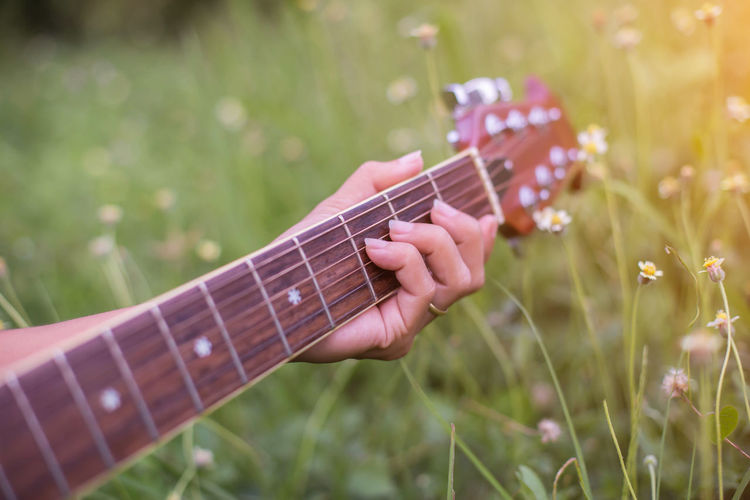 Hand holding guitar on field
