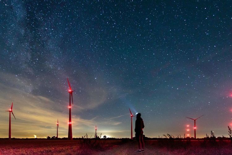 Rear view of man looking at illuminated windmills against star field