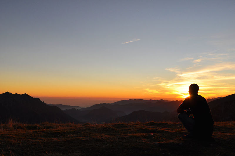 Silhouette man looking at mountains against sky during sunset